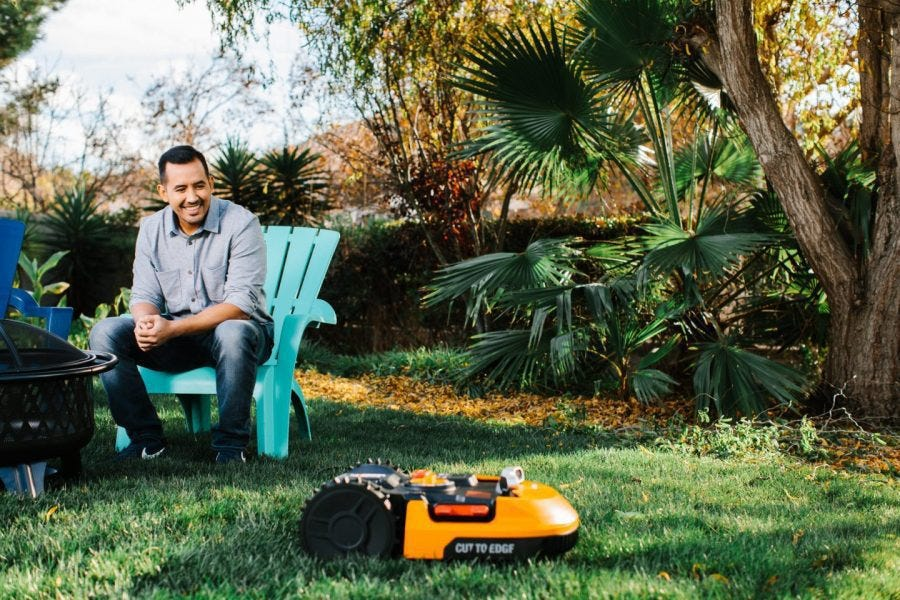 man sitting in yard watching Worx Landroid robotic mower auto mow the lawn