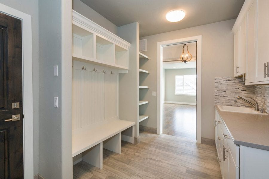 clean and empty home entry way with white walls, shelves and bench