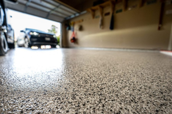 clean garage floor with garage door open and car entering