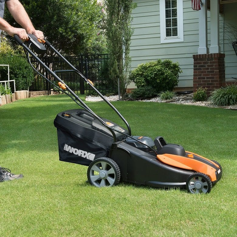person pushing Worx battery powered lawn mower on grass