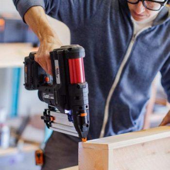 man using worx nitro cordless nail gun to drive nail into wood