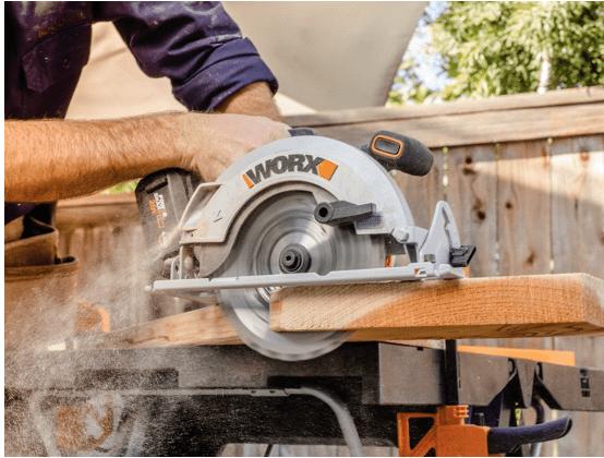 person using Worx circular saw to cut board