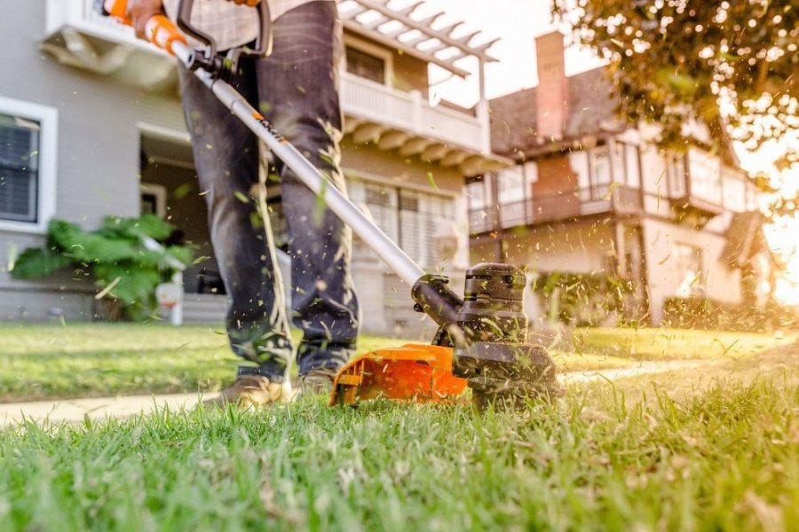 close up of person using worx battery powered weed eater to trim grass