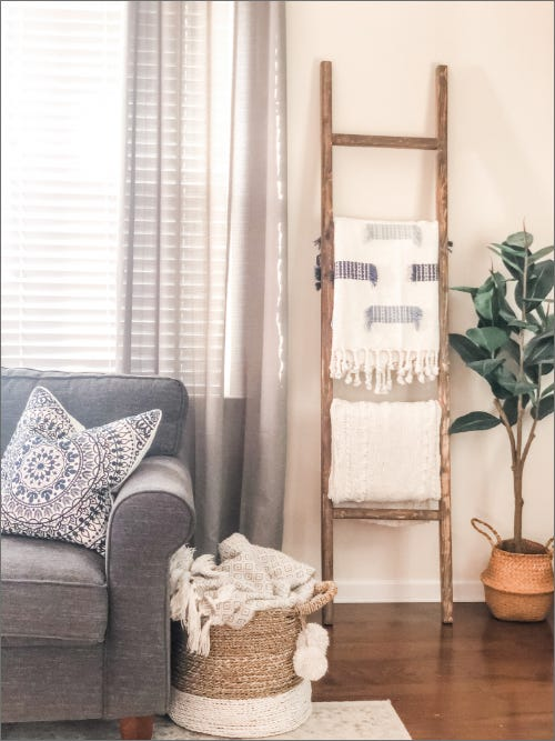 wooden blanket ladder holding blankets in a living room standing upright against a wall