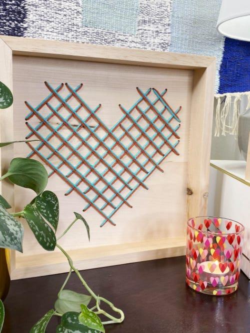 cross stitch yarn heart on wooden board