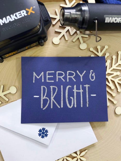 blue embossed holiday card that says merry and bright on table next to makerx heat gun and hub