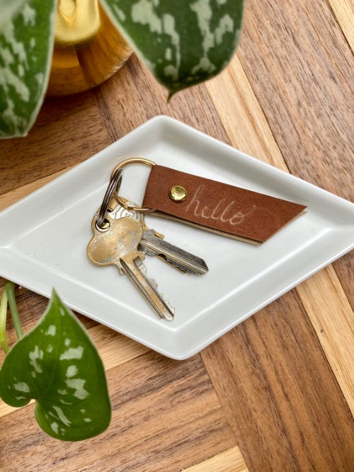 diy etched faux leather keychain and keys laying on white tray on top of wooden surface