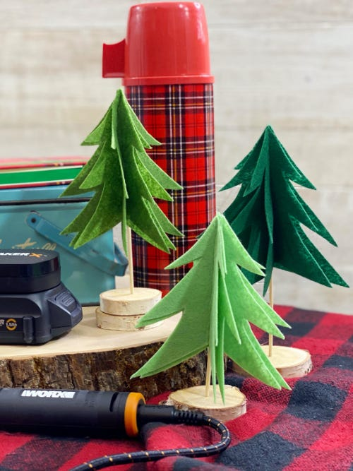 small green felt trees next to a red thermos
