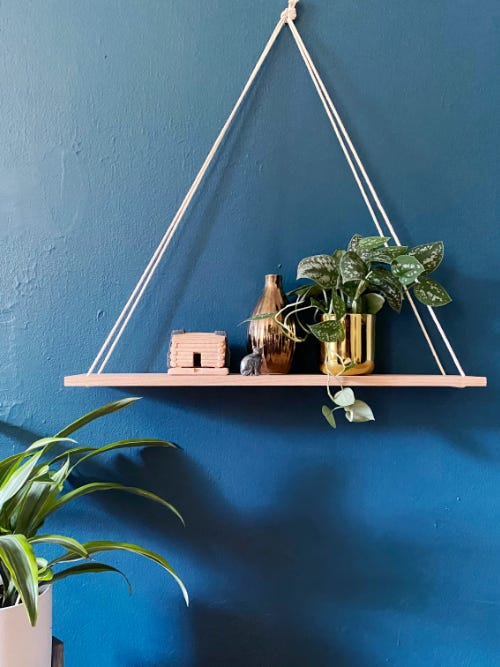 wooden hanging shelf in front of blue wall with plant and other items on the shelf
