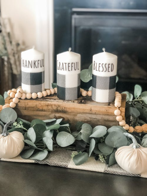 three white and plaid holiday candles on a wooden stand