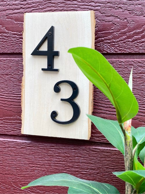 number 43 on a wood slice as a house address number