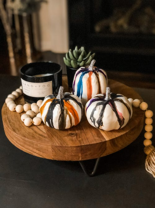 three pumpkins designed with melted crayons on a wooden table