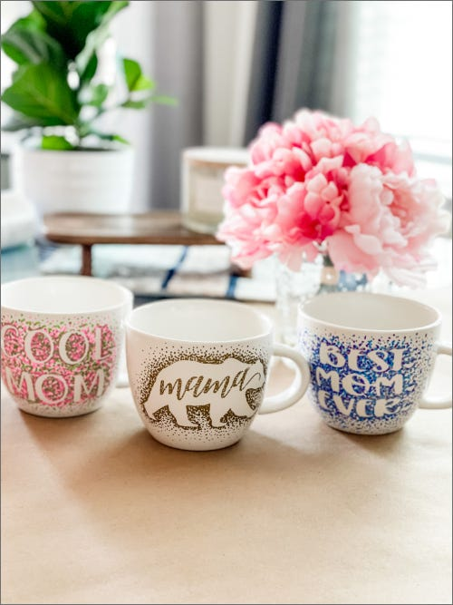 three custom painted mothers day coffee mugs on table in front of pink flowers