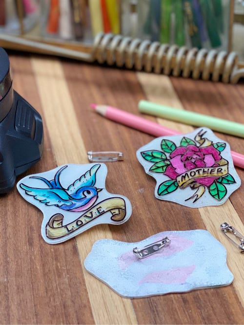 mothers day tattoo pins laying on wooden table next to colored pencils