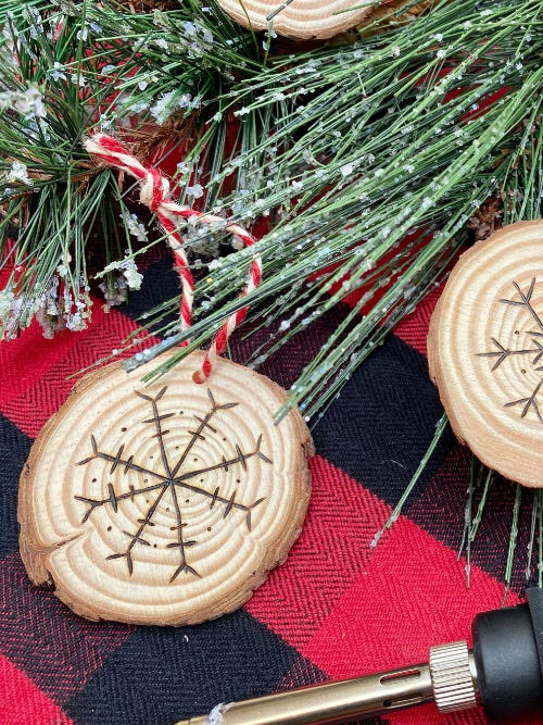 wooden tree ornament with snowflake design next to green pine tree needles