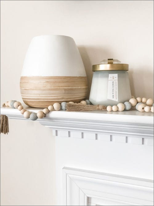 DIY wooden bead garland laying on white shelf next to lamp and covered candle