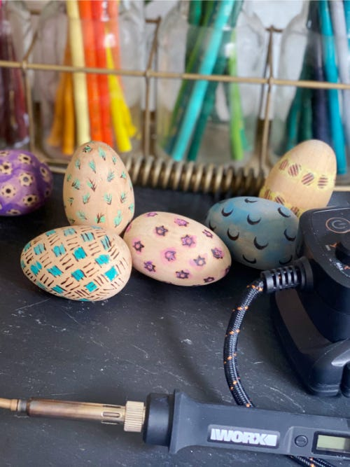 five wood burned easter eggs with colorful designs laying on table next to makerx wood and metal crafter